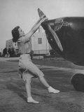 Woman Turning Propeller to Start Plane