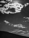 Sunshine Filled Clouds Against Dark Sky  Above Dark Dune in Middle of Kalahan Desert  Bechuanaland