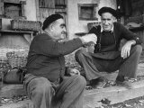 Two Older Basque Men Sitting on a Porch Toasting  as They Prepare to Drink Together