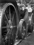 Workers Standing Amidst Large Metal Wheel Frames on Tractorstroi Tractor Factory Assembly Line
