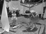 Suburban Mother Playing with Her Two Daughters While Hanging Laundry in Backyard