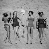 Four Models Showing Off the Latest Bathing Suit Fashions While Lying on a Sandy Florida Beach