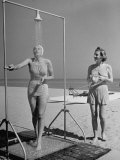 Shapely Sunbather Taking an Outdoor Shower as Woman Preparing for Her Turn  Looks On  at Beach