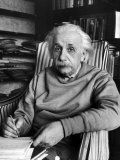 Scientist Albert Einstein Wearing Old Sweat Shirt  Sitting with Page of Equations in Home Library