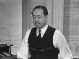 Writer Robert Benchley  Sitting at His Desk with a Small Wade of Paper in His Mouth