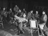 Songwriter Irving Berlin Reading Newspaper as Others Sit around Talking Papier Photo