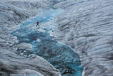 A Hiker Leaps across Ice Dotting a Glacial Pool