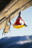 Rock Climber Bivouacked in His Portaledge on an Overhanging Cliff