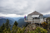 Woman Stands On The Edge Of A Backcountry Lookout Tower Overlooking The Cascade Mts Near Seattle