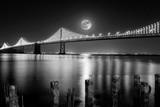 Super full moon rising in San Francisco Embarcadero pier over the Bay Bridge in the evening