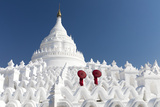 Two young Buddhist monks stand on the white walls of Hsinbyume Pagoda holding red umbrellas  Mingun
