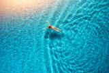 Aerial View of Swimming Woman in Mediterranean Sea at Sunset Papier Photo par Denbelitsky