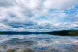 A cloudy sky reflects on a lake's surface