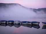 Fog rises from the water's surface at sunrise