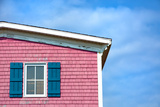 Architecture Detail of a Pink House with Blue Shuttered Window against Blue Sky