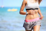 Runner Woman with Heart Rate Monitor Running on Beach with Watch and Sports Bra Top Beautiful Fit