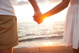 Summer Couple Holding Hands at Sunset on Beach Romantic Young Couple Enjoying Sun  Sunshine  Roman