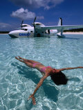 Female Floating in Crystal Waters in Front of Seaplane  Bahamas
