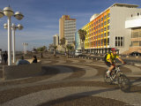 Cyclist on Jerusalem Beach Promenade with Dan Hotel Facade Decorated by Yaaqov Agam in Background