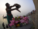 Woman Pouring Water Over Flowers on an Altar as a Religious Ritual  Varanasi  India