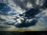Sun Rays Through Clouds Form a Spot on the Surface of the Water