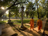 Two Buddhist Monks Walk Along the Siem Reap River at Sunrise  Cambodia