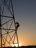 Silhouette of a Man Climbing a High Power Electric Line Tower  California