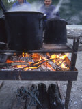Two Men at Camp Are Drying their Shoes under Camp Cook Fire
