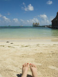 Womens Feet on the Beach with a View of the Ocean  Pier and Boats  Ambergris Caye  Belize