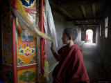 Young Monk Spinning a Prayer Wheel with Flags in a Monastery  Qinghai  China