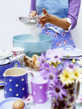 Woman Sieving Flour into a Bowl  Crockery & Eggs in Front