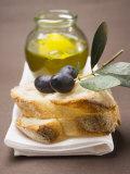 Olive Sprig with Black Olives on White Bread  Olive Oil Behind