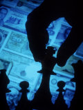 Hand Holding Chess Piece in Front of Currency