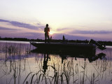 Man Standing in Boat Fishing