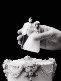 Female Hand Holding Wedding Cake Topper