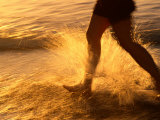 Close View of a Runners Legs Splashing Through the Surf