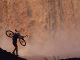 Silhouetted Cyclist Carrying Cycle Past Falls