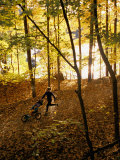 A Woman Pushes a Baby Stroller as She Jogs Through a Wooded Area