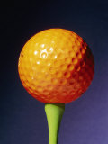 An Orange Golf Ball on a Green Tee with a Blue Background
