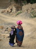 A Yemeni Woman and Child Carrying Bundles on Their Heads