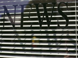 Afternoon Sun Casts Shadows Across the Word News Painted on a Window