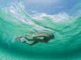 A Woman Snorkels under the Waves