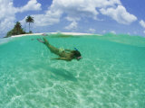 A Woman Snorkels in the Clear Blue Sea