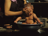 A Bhutanese Woman Bathes Her Baby in a Large Metal Bowl
