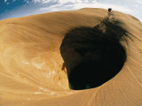 A Mountain Biker Cycles Around a Spectacular Crater in the Desert