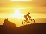 A Woman Rides Her Bike in the Sunset with Rock Cliffs in the Background