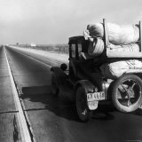Car Laden with Baggage on Desolate Track of Highway in Desert in Southern California