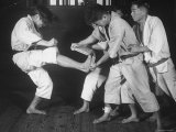 Japanese Karate Student Breaking Boards with Kick