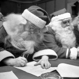 Santa Clauses Take a Written Examination For Diploma After Listening to Lectures