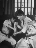 Japanese Karate Student Breaking Boards with Punch